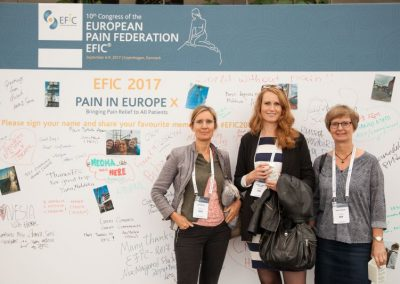 Three delegates posing in front of the memory wall at Pain in Europe X